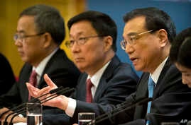 Chinese Premier Li Keqiang (R) is flanked by Vice Premiers Hu Chunhua (L) and Han Zheng during a press conference in Beijing, March 20, 2018. The premiere appealed to Washington to 'act rationally' and avoid disrupting trade.