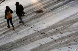 Pedestrians leave footprints in the snow as they cross a street in downtown Kansas City, Missouri,  Dec. 17, 2016. A new winter storm featuring freezing rain is expected to hit the nation's mid-section Friday, Dec. 13, 2017.
