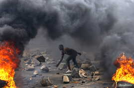 FILE - A protester sets up a  barricade during a protest against Burundi President Pierre Nkurunziza and his bid for a third term in Bujumbura, Burundi, May 22, 2015.