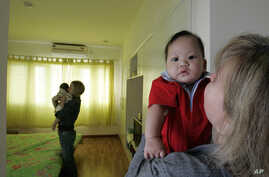 FILE - Monica DiGioacchino, right, of Alameda, Calif., holds her new adopted 7-month-old Vietnamese baby Patrick, as her roommate Tracy Sumner, background, of Richmond, Va., also holds her new adopted 5-month-old Vietnamese baby, Hanoi,Vietnam.