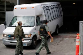 FILE - A van carrying asylum seekers from the border is escorted by security personnel as it arrives at immigration court, in San Diego, California, March 19, 2019.