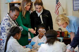 From left, school Principle Dana Bogle, first lady Melania Trump, Queen Rania of Jordan and Education Secretary Betsy DeVos talk with students during a science class at the Excel Academy Public Charter school in Washington, April 5, 2017.