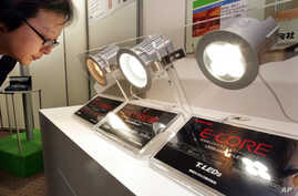 "FILE - Toshiba Corp. employee Shigeo Michishima looks at a high-efficiency LED light bulb ""E-CORE"" at the 17th Toshiba Group Environmental Exhibition in Tokyo."