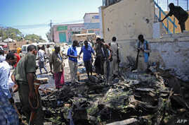 People look at the wreckage of a car bomb outside the Education Ministry in Mogadishu, April 14, 2015.               AFP PHOTO / MOHAMMED ABDIWAHAB