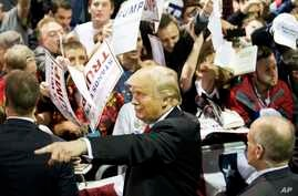 Republican presidential candidate Donald Trump gestures as signs autographs at a campaign event in Atlanta, Feb. 21, 2016.