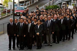 Hundreds of Hong Kong lawyers dressed in black march in silence in Hong Kong, June 27, 2014, to protest a recent Beijing policy statement they say undermines the Asian financial hub's rule of law.