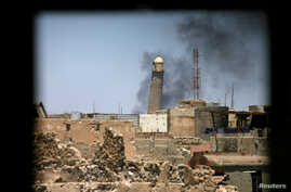 Al-Hadba minaret at the Grand Mosque is seen through a building window in the old city of Mosul, Iraq, June 1, 2017.