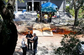Police officers talk to an employee at the Rehabilitation Center at Hollywood Hills in Hollywood, Fla., Sept. 13, 2017.  Several  patients at the sweltering nursing home died in Hurricane Irma's aftermath, authorities said Wednesday. The nursing home