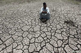 An Egyptian farmer squats down on cracked soil to show the dryness of the land due to drought in a farm formerly irrigated by the river Nile, in Al-Dakahlya, about 120 km (75 miles) from Cairo, June 4, 2013.