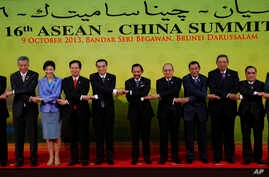 Chinese Premier Li Keqiang, 5th from left, joins hands with the ASEAN leaders for a group photo before the 16th Association of Southeast Asian Nations (ASEAN) - China Summit in Bandar Seri Begawan, Brunei, Oct. 9, 2013.
