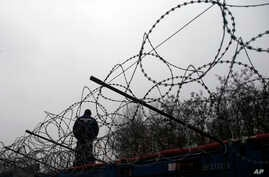 """A Hungarian police officer stands guard at Serbia's border with Hungary near a makeshift camp for migrants in Horgos, Serbia, Wednesday, Feb. 8, 2017. European Commission Vice-President Frans Timmermans said Wednesday that it is """"highly urgent"""" for c"""