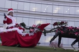 Robotic reindeer pull a Christmas sleigh in this screenshot from a Boston Dynamics video.