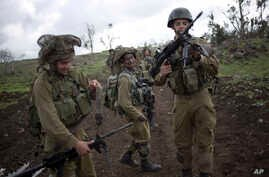 Israeli soldiers of the Golani brigade adjust their weapons during training near the border with Syria in the Israeli-controlled Golan Heights, Feb. 26, 2014.