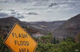 In this photo provided by Santa Barbara County Fire Department, a flash flood area sign is posted, as evacuations have been issued for several fire-ravaged communities in Santa Barbara, California, Jan. 8, 2018.