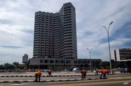 FILE - The Melia Cohiba hotel stands tall as workers repaint pavement markings along the Malecon in preparation for Pope Francis' visit in Havana, Cuba. President Trump is preparing to tighten the six-decade trade embargo on Cuba on Monday, March 4,
