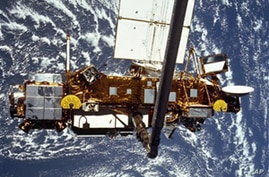 In this image provided by NASA this is the STS-48 onboard photo of the Upper Atmosphere Research Satellite (UARS) in the grasp of the RMS (Remote Manipulator System) during deployment, from the shuttle in September 1991. The satellite is 35 feet long