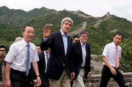 U.S. Secretary of State John Kerry, center, and U.S. Treasury Secretary Jacob Lew, second from right, wave to journalists as they visit to Badaling Great Wall of China in Beijing, China, July 8, 2014.