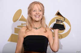 """Maria Schneider poses in the press room with the award for best contemporary classical composition for """"Schneider, Maria: Winter Morning Walks"""" at the 56th annual GRAMMY Awards at Staples Center, Jan. 26, 2014, in Los Angeles."""