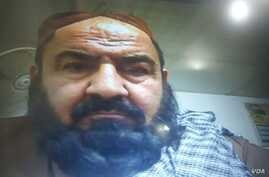 Handout photo showing Mullah Mansur at Pakistan's Federal Investigation Agency (FIA) immigration office on the Pakistan-Iran-Afghan border. He passed through the usual entry/exit booth in front of a computer, five hours before his killing.
