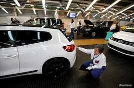 Employees work on an assembly line at the Volkswagen factory in Palmela, Portugal, Dec. 9, 2016.