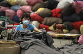 FILE - A volunteer sews blankets made from recycled plastic bottles at The Tzu Chi Foundation factory in Taipei, Taiwan. Taiwanese exports are falling, driving the island's economy into recession.
