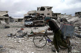 A man walks with his bicycle at a damaged site in the besieged town of Douma, eastern Ghouta, in Damascus, Syria March 30, 2018.