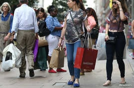 FILE - Shoppers carry bags in London, Britain, August 25, 2016. The falling value of the British pound vs. other currencies is making London more attractive to bargain-hunters.