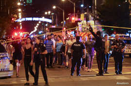 People leave an area cordoned off by police near the scene of a shooting incident in Toronto, Canada, July 22, 2018.