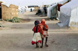 Ami and Ashbu, both three-years-old, walk  arm in arm in the Zafaye refugee camp, some 15 kms (10 miles) from downtown N'djamena, Chad, March 11, 2015
