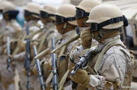 FILE - Saudi troops stand attention at their base in Yemen's southern port city of Aden, Sept. 28, 2015.