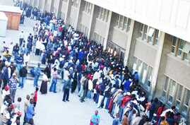 Zimbabweans gather and queue outside a Home Affairs Department office in South Africa to apply for new residence permits
