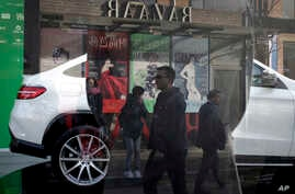 FILE - People are reflected on a window as they walk past fashion magazine posters near a Mercedes-Benz SUV model on display at a showroom in Beijing, Oct. 26, 2015. Wealthy Chinese remain the No. 1 buyers of luxury products worldwide, according to a