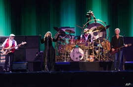 John McVie, from left, and Stevie Nicks  and Lindsey Buckingham of Fleetwood Mac performs at the Isle of Wight Festival, in Newport, Isle of Wight, England, June 14, 2015.