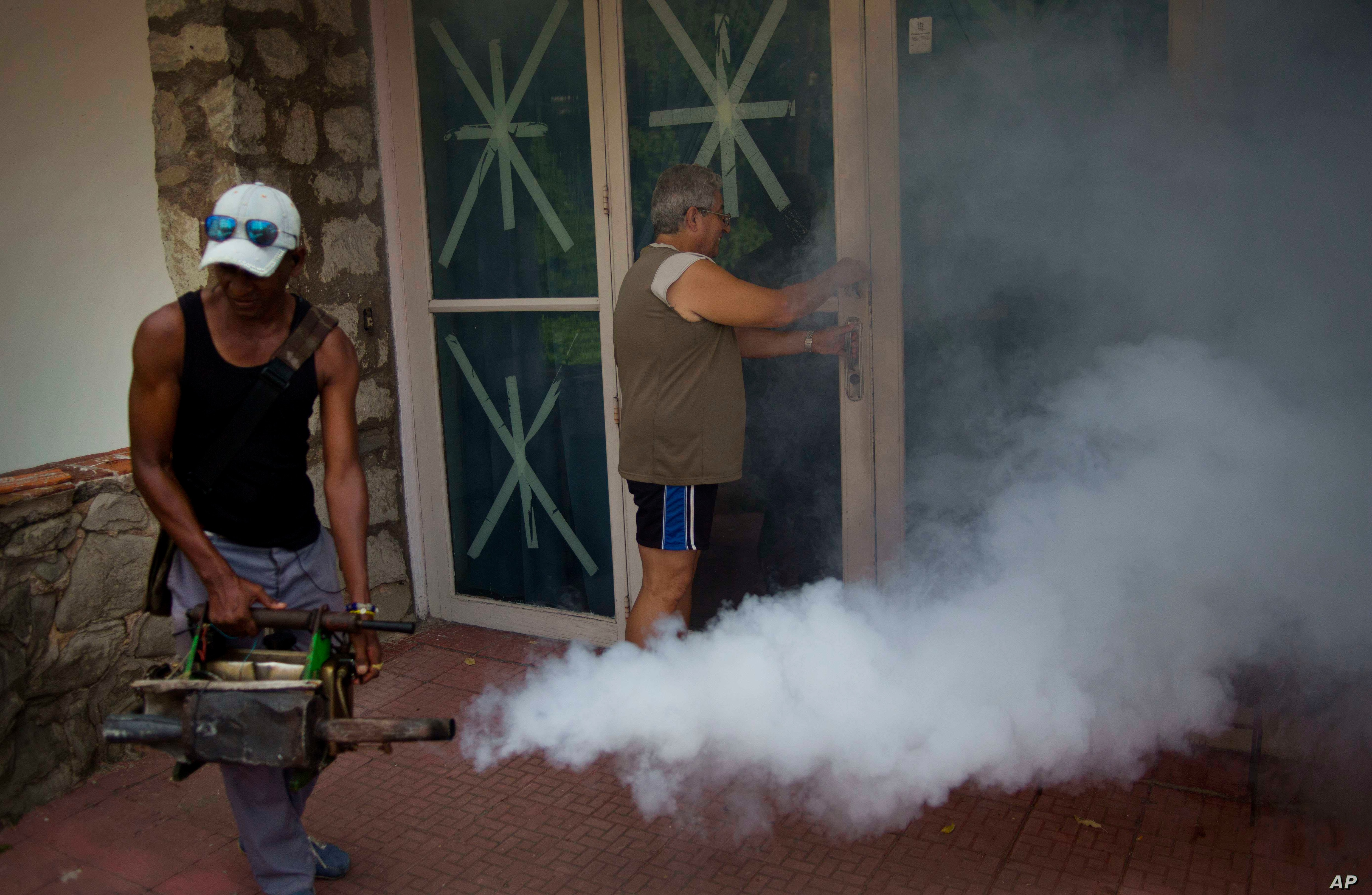 FILE - A government fumigator sprays a home for mosquitos in Havana, Cuba, Aug. 26, 2016.