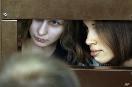 Maria Alekhina, left, and Nadezhda Tolokonnikova, members of punk group Pussy Riot, consult with their lawyers from within their courtroom cage, Moscow, July 30, 2012.