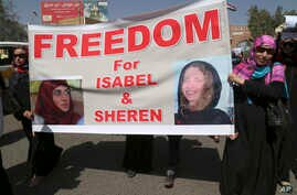 FILE - Yemeni activists held a banner with pictures of kidnapped French Isabelle Prime (r) and her Yemeni colleague during a protest for their release in Sanaa, Yemen, March 5, 2015.