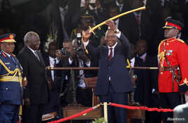 Kenya's President Uhuru Kenyatta (C) displays the special sword that he received to represent his instruments of power and authority from his predecessor, Mwai Kibaki (2nd L), after his official swearing-in ceremony at Kasarani Stadium in the capital