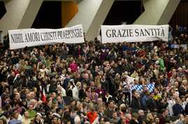 """Faithful hold banners reading in Latin """"Nihil amori Christi praeponere"""" (Prefer nothing to the love of Christ), left, and in Italian """"Grazie Santita' """" (Thank you Your Holiness) during Pope Benedict weekly general audience at the Vatican Feb. 13, 201"""