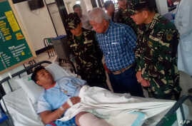 Philippines Defense Secretary Voltaire Gazmin (2nd R) and military chief General Hernando Iriberri (R) visit one of the 53 wounded soldiers at a military hospital in Zamboanga on the southern Philippine island of Mindanao on April 10, 2016, a day aft