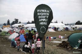 A banner placed by activists is displayed on a street sign at a makeshift camp for refugees and migrants at the Greek-Macedonian border, near the village of Idomeni, Greece, March 17, 2016.