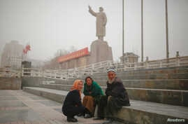 Ethnic Uighurs sit near a statue of China's late Chairman Mao Zedong in Kashgar, Xinjiang Uighur Autonomous Region, China, March 23, 2017.