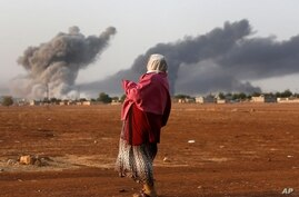 Syrian Kurd Kiymet Ergun, 56, standing in Mursitpinar on the outskirts of Suruc, at the Turkey-Syria border, watches while thick smoke rises following an airstrike by the US-led coalition in Kobani, Oct. 13, 2014.