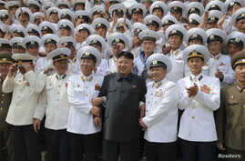 North Korean leader Kim Jong Un (C) poses with officers and sailors of Korean People's Army in this undated photo released by North Korea's Korean Central News Agency (KCNA) in Pyongyang June 16, 2014.