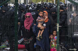 Migrants are sent back by Hungarian riot police at the border crossing with Serbia in Roszke, Hungary September 16, 2015. Hungarian police fired tear gas and water cannon at protesting migrants demanding they be allowed to enter from Serbia on the se