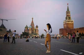 FILE - A young woman checks her smartphone at Red Square in Moscow, Russia, July 25, 2016. Russians may haver their access to Facebook blocked if the social media giant does not start storing Russian user data locally.