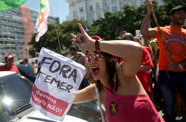 """A demonstrator holds a sign that reads """"Temer Out"""" during a protest against Brazil's President Michel Temer on Copacabana beach, in Rio de Janeiro, Brazil, Sunday, Sept. 4, 2016."""