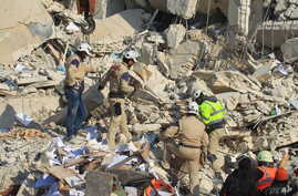FILE - Civil defense members search for survivors at a site hit yesterday by what activists said were airstrikes carried out by the Russian air force in Idlib city, Syria, Dec. 21, 2015.