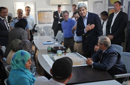 U.S. Secretary of State John Kerry, center right, greets a group of Syrian refugees during a joint meeting with Jordanian Foreign Minister Nasser Judeh, sitting at right, at the Zaatari refugee camp near Mafraq, Jordan, July 18, 2013.