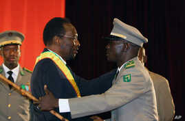 Mali's Interim President Dioncounda Traore, left, is congratulated by coup leader Amadou Sanogo after being sworn in at a ceremony in Bamako, Mali, April 12, 2012.