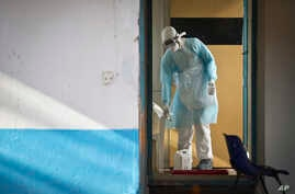 FILE - A medical worker wearing full protective equipment decontaminates a cup used by a man being quarantined after coming into contact in Uganda with a carrier of the Marburg Virus, a hemorrhagic fever from the same family as Ebola, at the Kenyatta